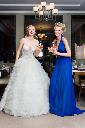 The bride and bridesmaid (maid of honor) are celebrating with ...